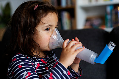 Close-up of asthmatic girl using inhaler in living room at home - p300m2189214 by Valentina Barreto