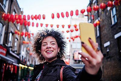 Smiling hipster woman taking selfie through smart phone at Chinatown - p300m2273654 by Angel Santana Garcia