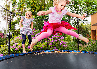 Girls jumping on trampoline - p312m1192878 by Susanne Kronholm