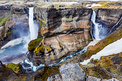 The stunning earthy colors and rock formations along with unmelted snow resting in the bottom of the Haifoss valley among two waterfalls.  Natural beauty in one of Iceland's great hiking viewpoints; Iceland - p442m2008948 by Alanna Dumonceaux