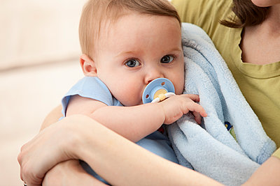 Caucasian baby boy with pacifier in mother's arms - p555m1478158 by Mike Kemp