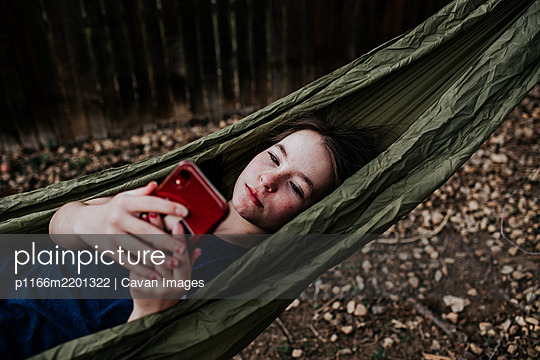 Teen girl laying in hammock playing on cell phone - p1166m2201322 by Cavan Images