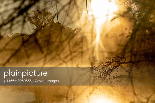 Sunrise canoe ride on foggy river. - p1166m2269653 by Cavan Images