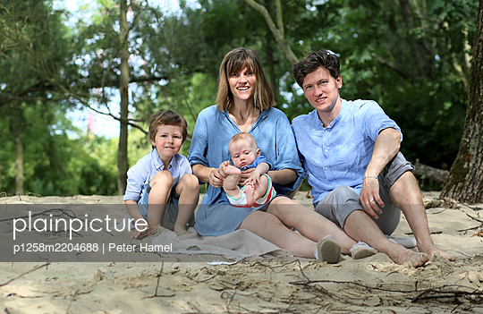 Family with two children on the beach - p1258m2204688 by Peter Hamel