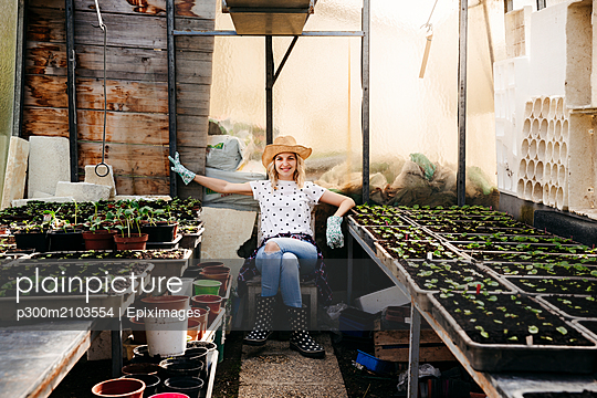 Young woman gardening in a greenhouse - p300m2103554 by Epiximages