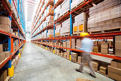Warehouse worker walking in an aisle in warehouse - p1315m1147775 by Wavebreak