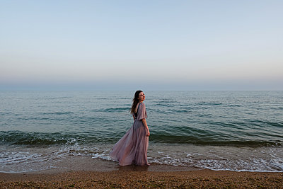 Woman standing on beach - p1363m2126655 by Valery Skurydin