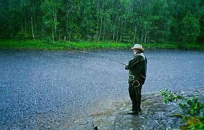Man fishing in rain - p1418m2007545 by Jan Håkan Dahlström