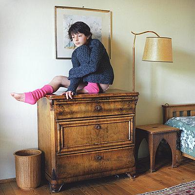 A chilg sitting on a dresser - p1610m2185441 by myriam tirler