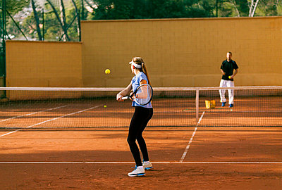 Teenage girl training tennis with her teacher - p300m1356588 by Valentina Barreto