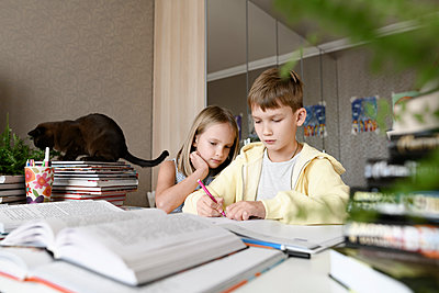 Brother and sister with a cat sitting at table at home doing homework together - p300m2154875 by Ekaterina Yakunina