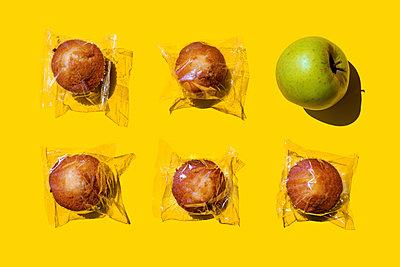 Studio shot of single apple and five plastic wrapped muffins - p300m2198443 by Gemma Ferrando