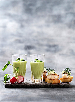 Glass of pea soup and scallop canapes - p429m746992f by Line Klein