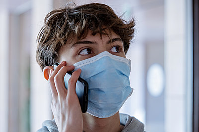 Close up of teenage boy with medical mask talking on smartphone during lockdown - p623m2186297 by Frederic Cirou