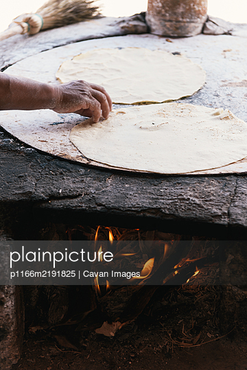 Side view of fresh tortilla cooking on an open fire comal - p1166m2191825 by Cavan Images