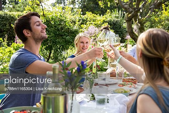 Freunde stoßen auf der Gartenparty mit Weißwein an - p788m1165304 von Lisa Krechting