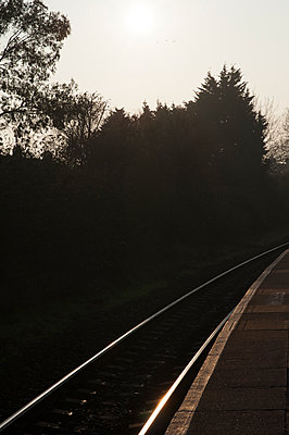 Train platform and single track in early morning light - p1047m1159914 by Sally Mundy