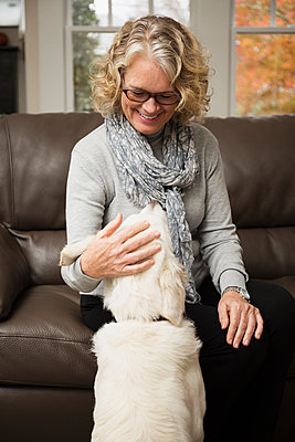 Senior woman with dog in living room - p1427m2283137 by Roberto Westbrook