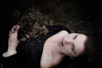 Portrait of melancholic woman lying on forest floor - p300m1205922 by Jana Mänz