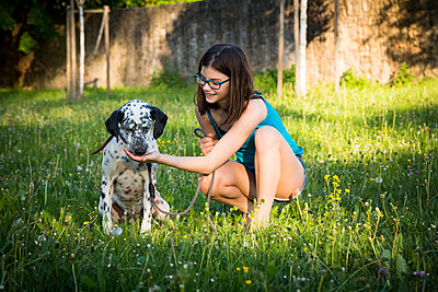 Girl feeding Dalmatian in the garden - p300m1588000 von Larissa Veronesi