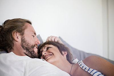 Smiling heterosexual couple resting on bed at home in bedroom - p300m2224954 by LOUIS CHRISTIAN