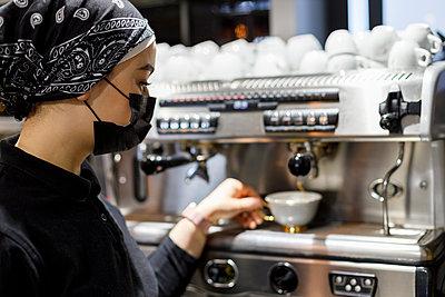 Female barista preparing coffee while working at cafe - p300m2281885 by Ignacio Ferrándiz Roig