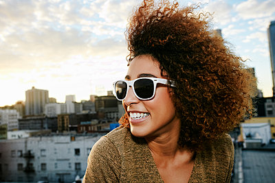 Portrait of smiling Hispanic woman on urban rooftop at sunset - p555m1472937 by Peathegee Inc