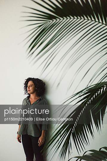 Black-haired woman, palm tree in the foreground - p1150m2210409 by Elise Ortiou Campion