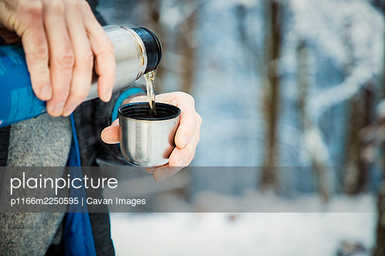 man pouring hot tea in winter forest - p1166m2250595 by Cavan Images