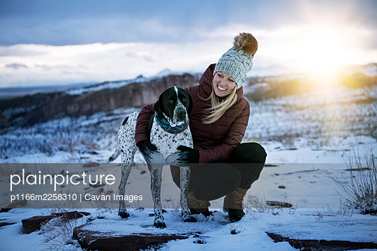 Happy woman hiking with dog during vacation - p1166m2258310 by Cavan Images
