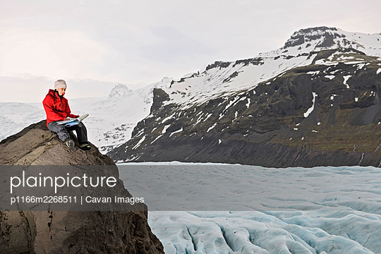 Female hiker reading map on rock above glacier - p1166m2268511 by Cavan Images