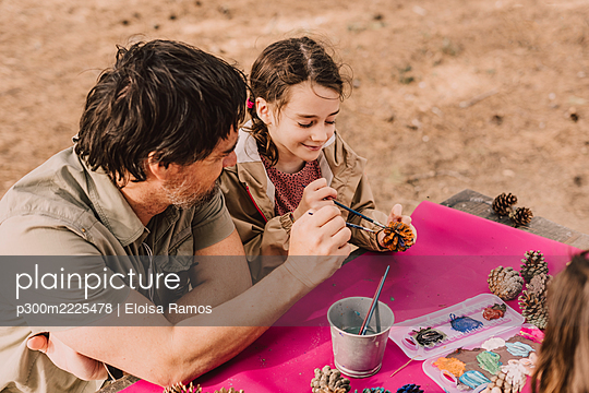 Smiling girl coloring pine cone with father while sitting at picnic table in park - p300m2225478 by Eloisa Ramos