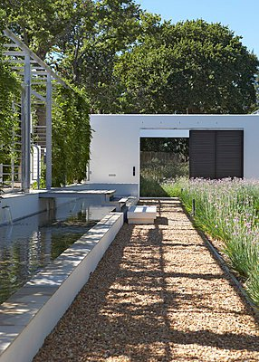 Contemporary landscaping - sunny gravel path edged by meadow and water feature - p1183m995791 by Van Berge, Alexander