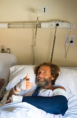 Middle-aged man in hospital with one broken arm and raising the other arm with positive attitude - p1656m2248593 by Javier Martinez Bravo