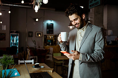 Smiling male entrepreneur using smart phone while having coffee in coffee shop - p300m2277374 by Rafa Cortés