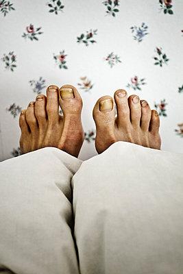 A pair of feet sticking out from under the covers in bed (Ett par fötter sticker fram under täcket i säng) - p847m673079 by Anna Molander