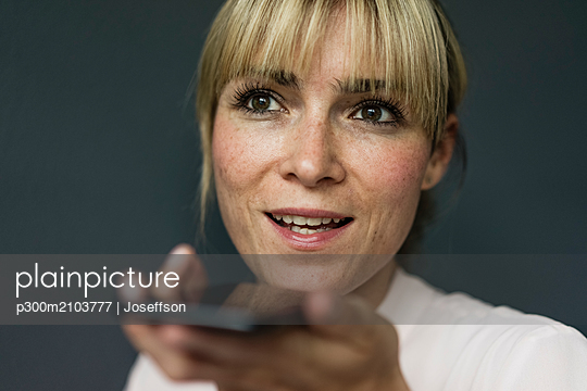 Portrait of a blond businesswoman, using smartphone - p300m2103777 by Joseffson