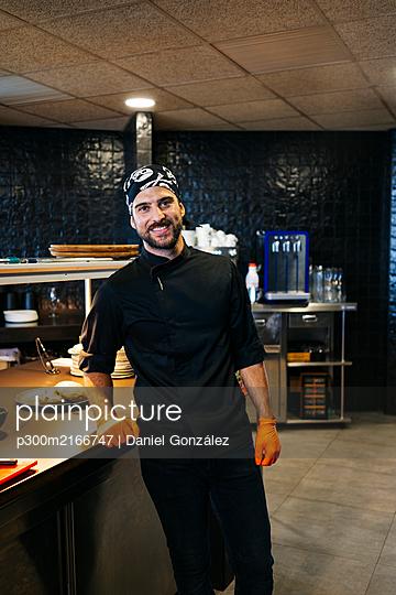 Portrait of smiling chef in restaurant kitchen - p300m2166747 by Daniel González