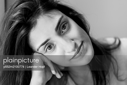 Dark-haired woman day dreaming - p552m2100774 by Leander Hopf
