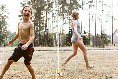 Cheerful kids playing with water - p312m2051578 by Lina Arvidsson