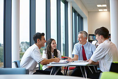 Group of teenagers working with teacher in school class - p429m884625f by Phil Boorman