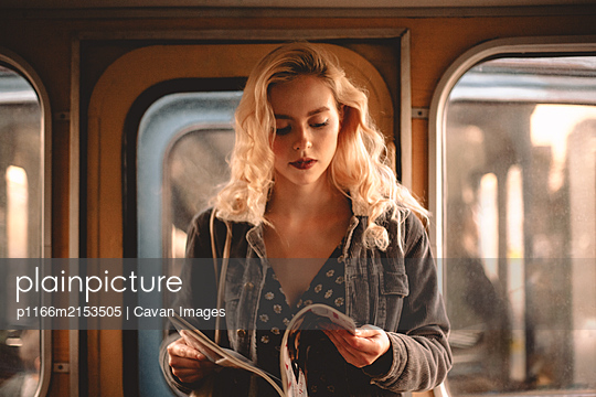 Young woman reading magazine while traveling in subway train - p1166m2153505 by Cavan Images