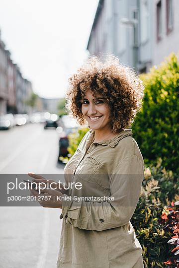Woman in the city using smartphone - p300m2012787 von Kniel Synnatzschke