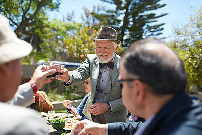 Senior man in suit and bow tie toasting friends with wine at sunny garden party - p1023m1583956 by Trevor Adeline