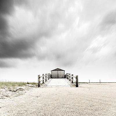 Kleiner Pfahlbau vor schnell ziehenden Wolken am Strand von Sankt Peter-Ording - p1162m2115381 von Ralf Wilken