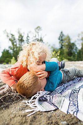 Two brothers wrestling while playing during picnic - p1166m2202000 by Christopher Kimmel / Alpine Edge Photography