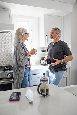 Senior couple talking and drinking coffee in kitchen - p1192m2109768 by Hero Images