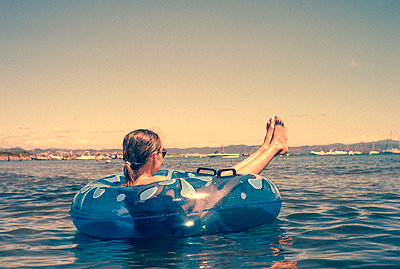Girl chills out in a rubber dinghy - p1654m2280254 by Alexis Bastin