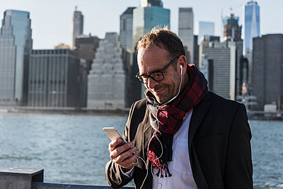 USA, Brooklyn, smiling businessman with earphones looking at his smartphone - p300m1205965 by Uwe Umstätter