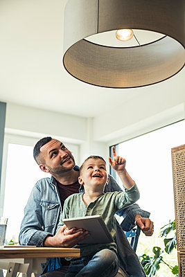 Smiling boy pointing at pendant light while sitting with father in smart home - p300m2286937 by Uwe Umstätter
